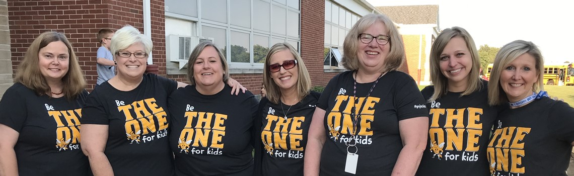 "A group of female teachers wears black shirts with yellow lettering that says ""Be The One For Kids""."